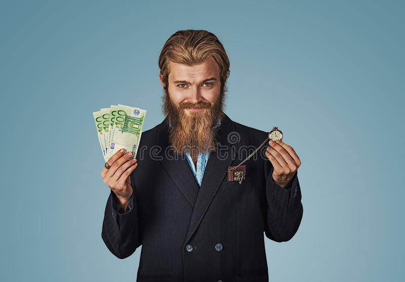 Guy is a lucky winner holding a pile of money and a watch stock photography