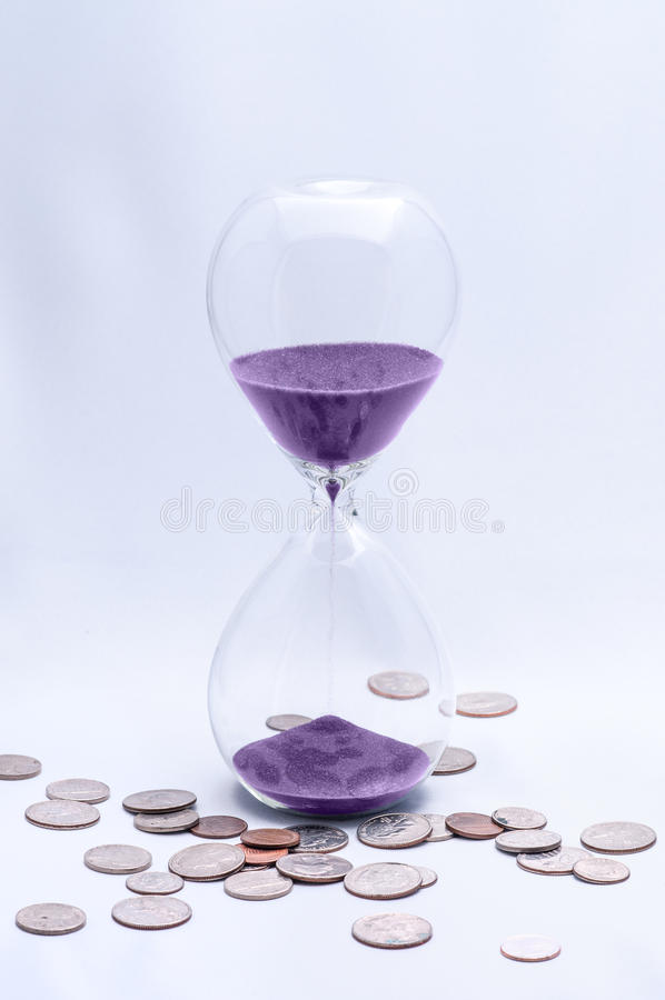 Time is Money hourglass. Hourglass with Coins - representing Time is Money royalty free stock images