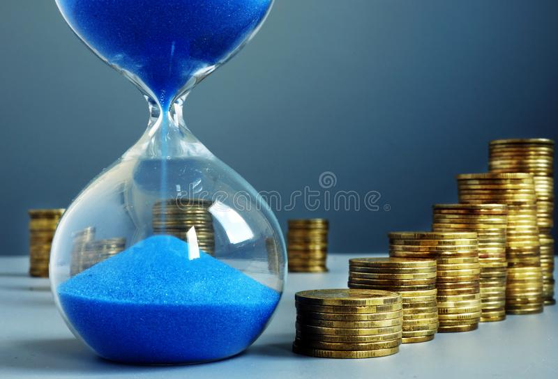 Time and money. Hourglass and stack of coins as savings. Time and money concept. Hourglass and stack of coins as savings stock photography
