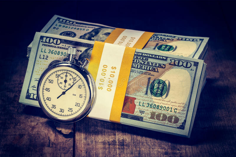Time is money. Loan concept background. Vintage retro effect filtered hipster style image of stopwatch and stack of new 100 US dollars 2013 edition banknotes royalty free stock photos