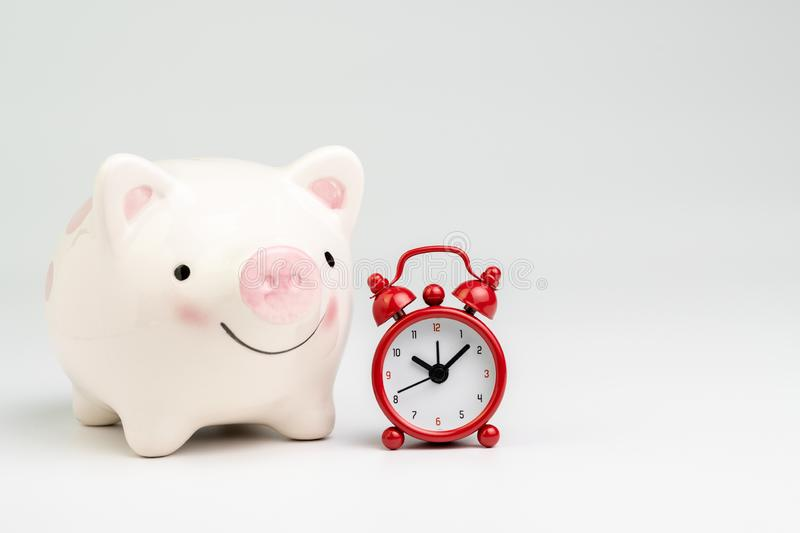 Time is money or long term savings and investment concept, smile pink piggy bank with red alarm clock on white background with. Copy space royalty free stock photo