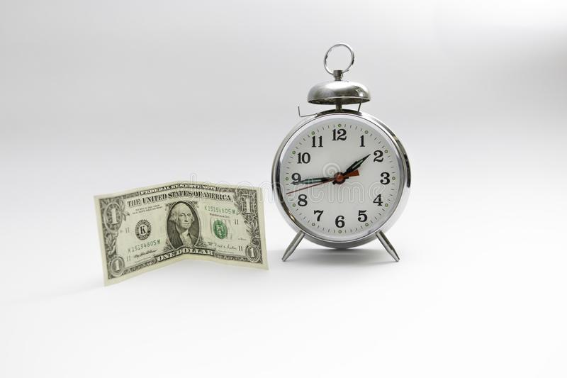 Time is money. One dollar bill standing next to a big clock royalty free stock photos
