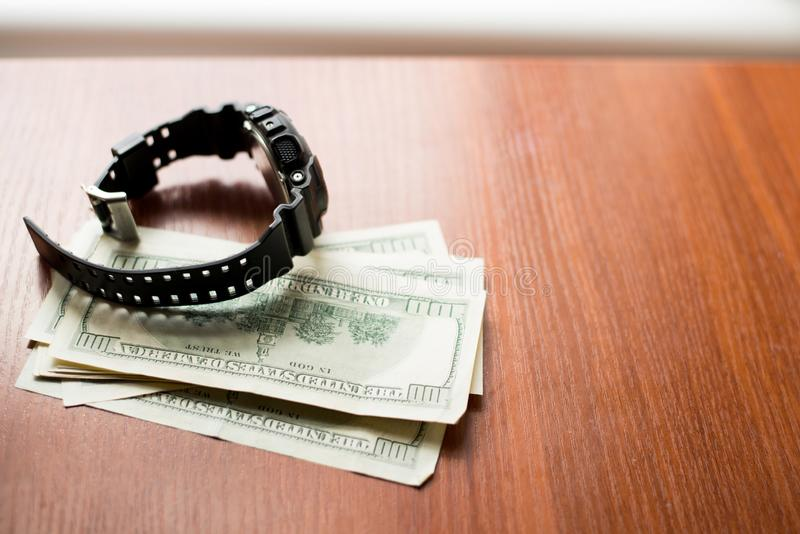 Time is money. One hundred dollars and black watch on wooden table stock photography