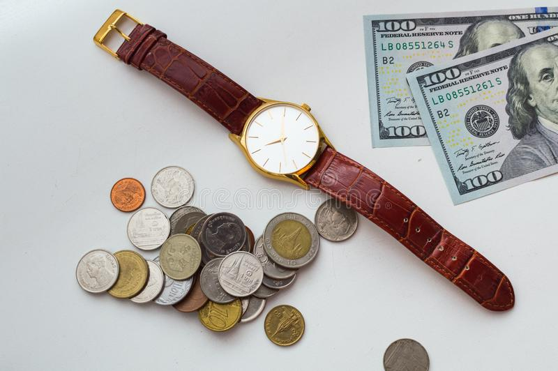 Time is money. Wrist watch with dollar bills and coins on a white background royalty free stock image
