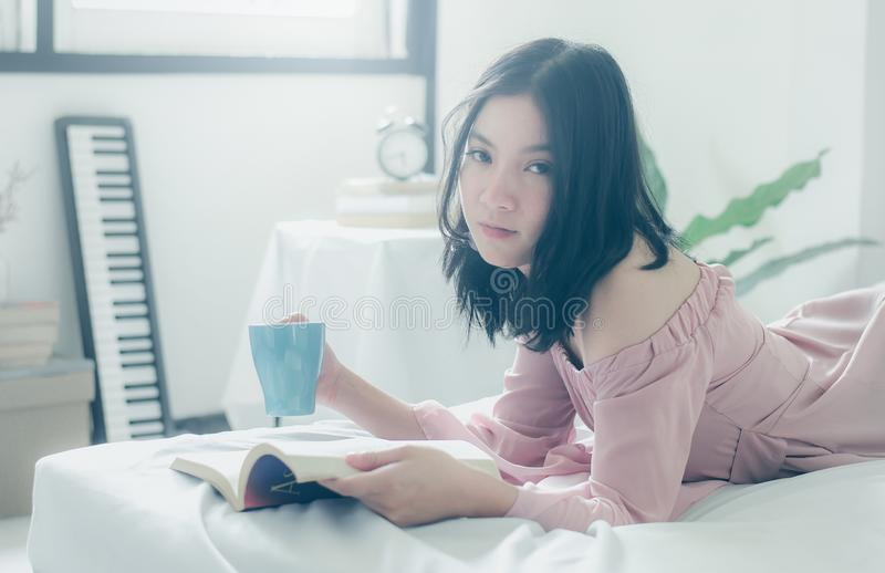 Time for myself. Comfort and relaxation. Pretty young asian woman drinking tea or coffee and reading book while sleeping royalty free stock images
