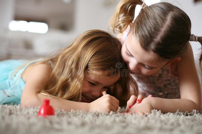Time for nails. Little girls. Close up image of two little girls. Focus on girls stock images