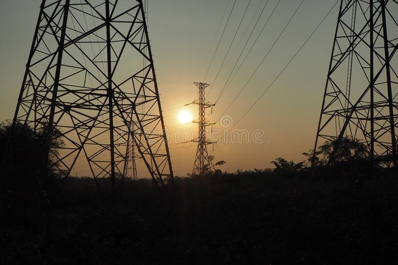The sun is near the horizon. Light through the high voltage pylon royalty free stock images