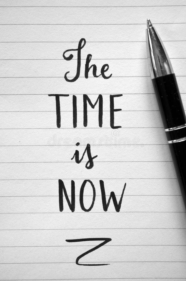`The time is now` hand-lettered in notebook. On wooden desk with pen and cup of coffee royalty free stock photography