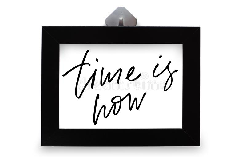 Time is now. Handwritten text. Modern calligraphy. Inspirational quote. Black photo frame. Isolated on white stock images