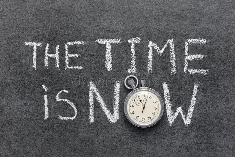 Time is now. The time is now phrase handwritten on chalkboard with vintage precise stopwatch used instead of O stock image
