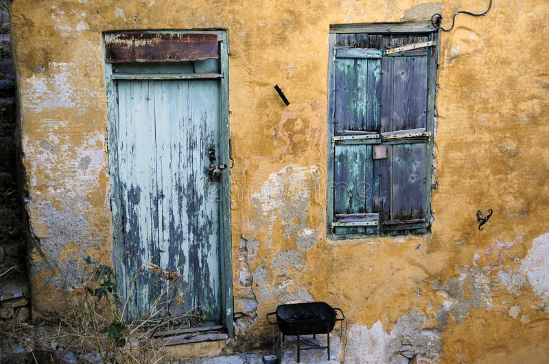 Time. An old house on the island of Symi, Dodecanese, Greece, with the fading paint, rust and weathering of the walls serving as silent reminders of the stock photos