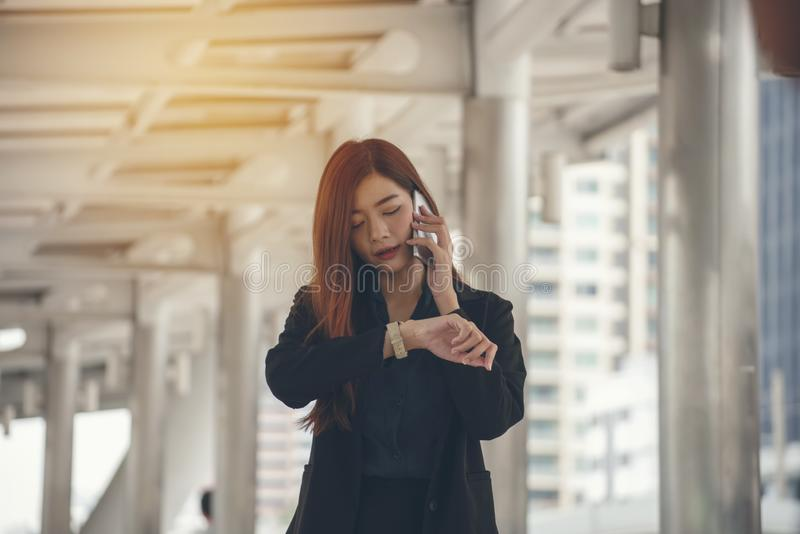 Time out concept.Urgent work,business woman seeing wrist watch and using mobile phone before meeting.Smart woman check the. Schedule before going to the office stock photo