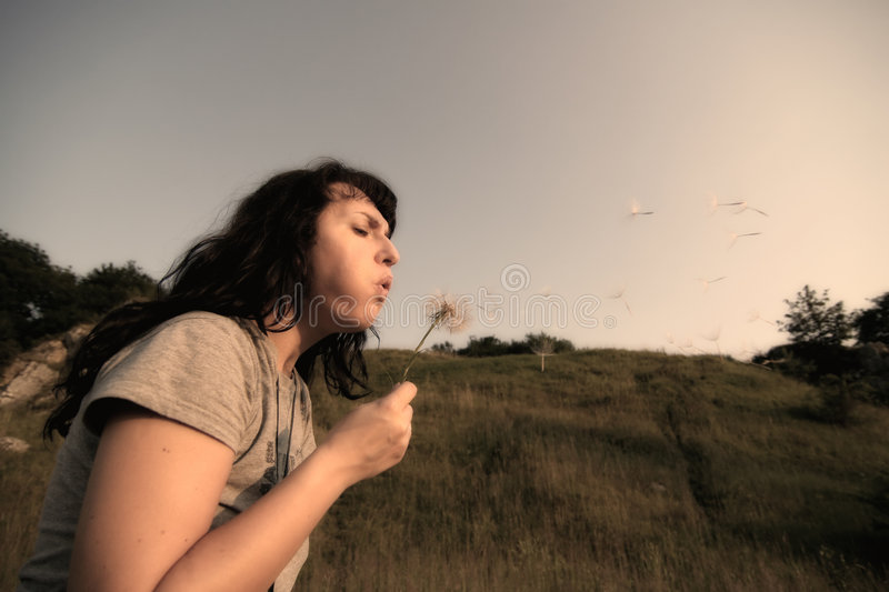 Time Pass By - Idea. Woman blowing on the blow-ball royalty free stock photos