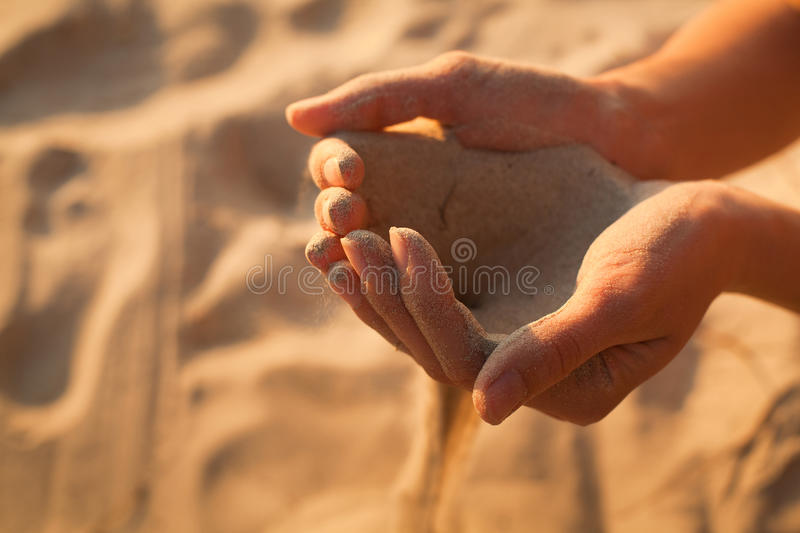 Time passing. Sand in the hands stock image