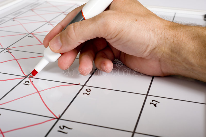 TIme Passing. A hand holding a dry erase marker X'ing out or crossing out days of the month on a calendar. Passing of time concept stock image
