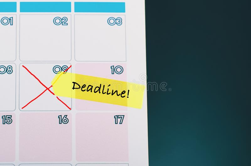 Cropped hand and yellow sticky paper with word DEADLINE on calendar stock images