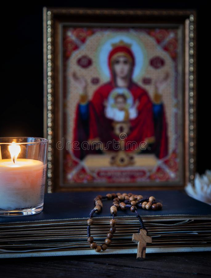 The time for prayer. Wooden Rosary on an ancient prayer book. Icon of the Mother of God and Jesus. Lighted candle royalty free stock photo