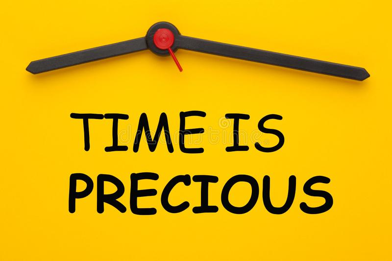 Time Is Precious. Text with clock on yellow dial royalty free stock image