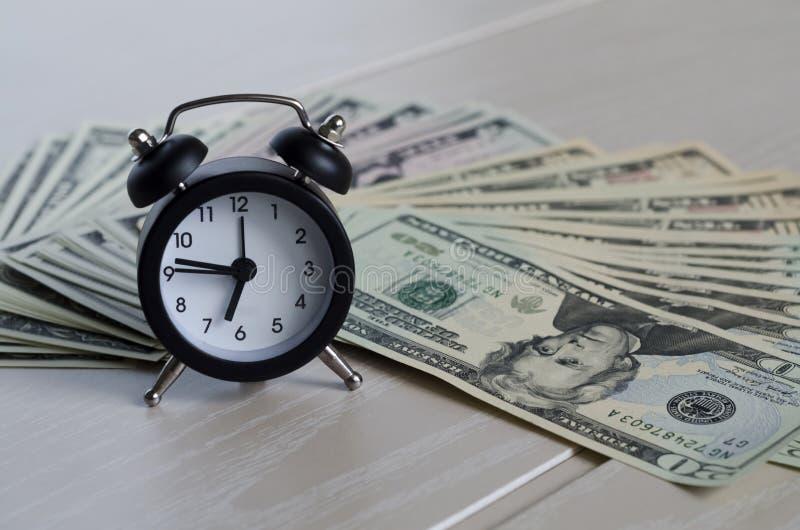 Time ?r pengar tid är värde pengarna Tid ?r mer v?rdefull ?n pengar klocka och dollar sedlar för affärsidé royaltyfria foton