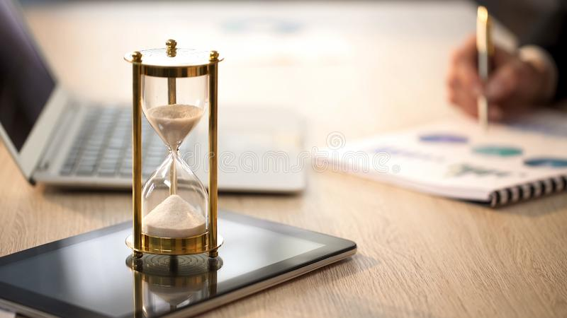 Time is running in hourglass, female manager checking graphs at office desk royalty free stock images