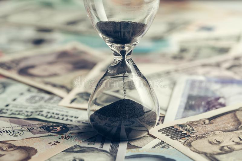 Time running or long term investment concept with sand glass or hour glass on many countries international banknotes, US Dollar, royalty free stock images