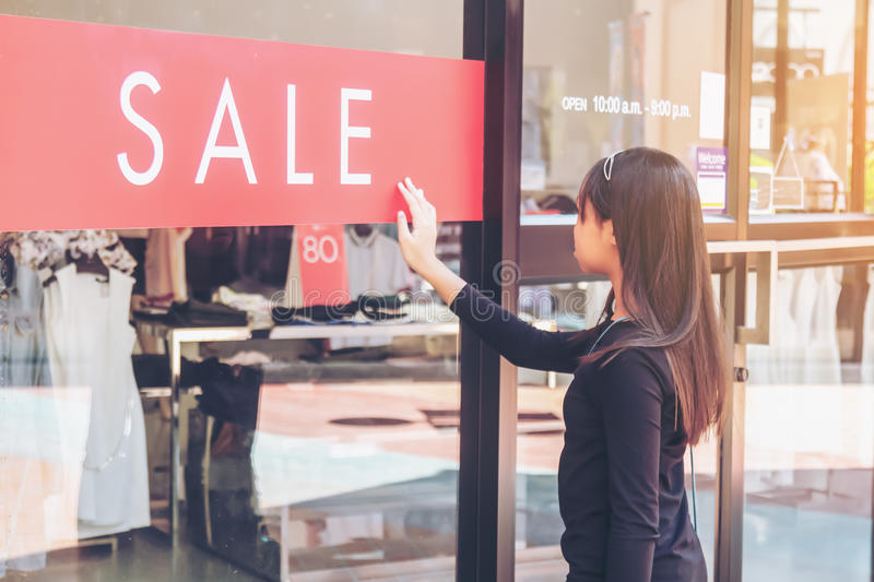 Time for sale. Asian girls look at the sale discount tag in front of the shop stock photography