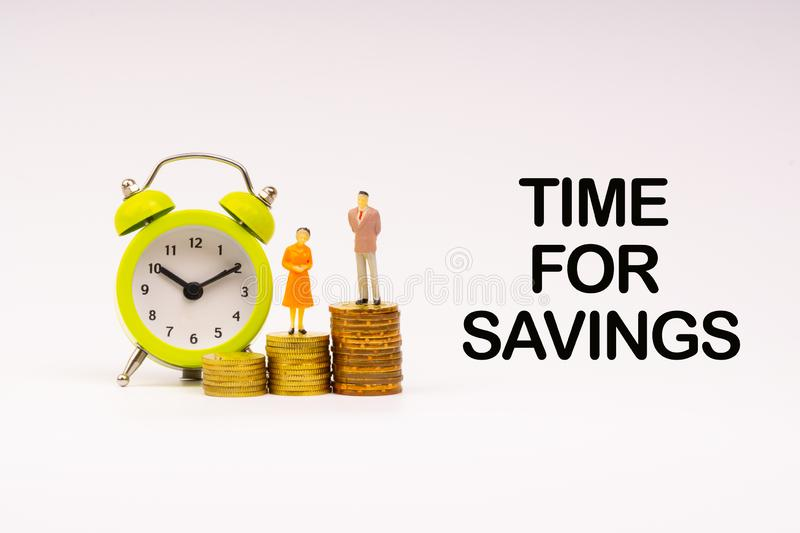 TIME FOR SAVINGS inscription written, alarm clock, coins and businessman miniature royalty free stock images
