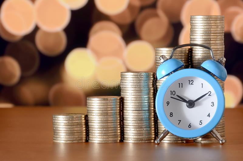 Time for savings money concept, banking and business idea. Alarm clock and Money coin stacks in grow graph. Finance sustainable development and economic growth royalty free stock image