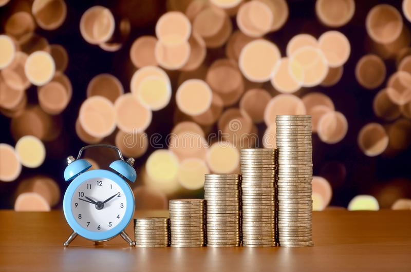 Time for savings money concept, banking and business idea. Alarm clock and Money coin stacks in grow graph. Finance sustainable development and economic growth royalty free stock photography