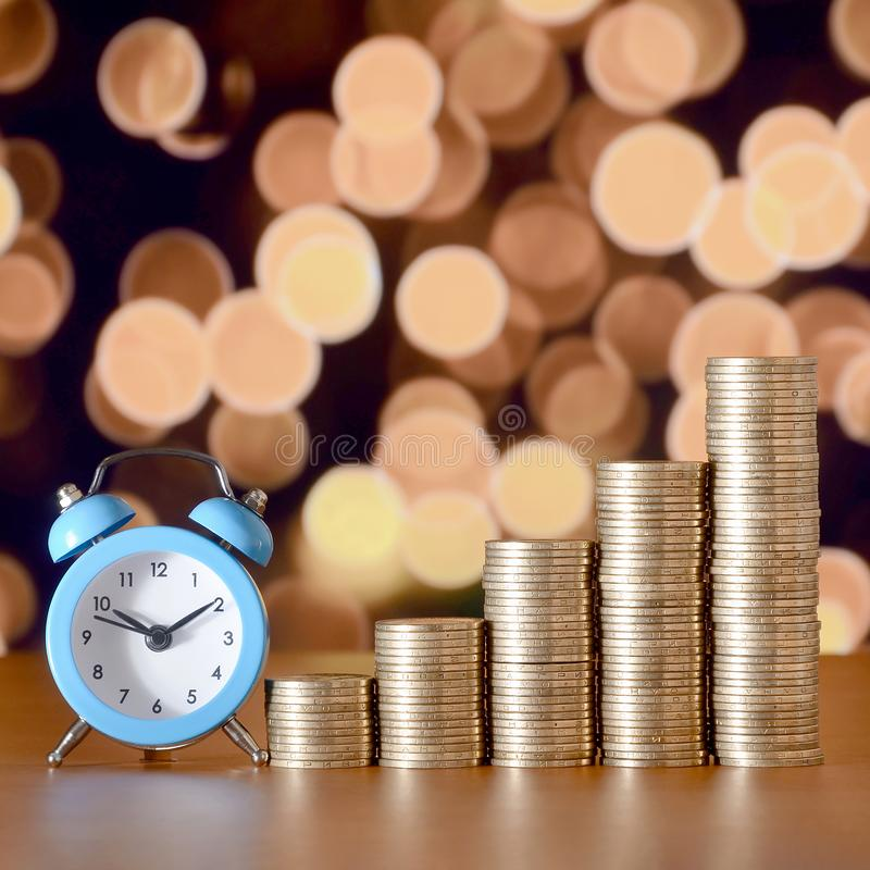 Time for savings money concept, banking and business idea. Alarm clock and Money coin stacks in grow graph. Finance sustainable development and economic growth royalty free stock images