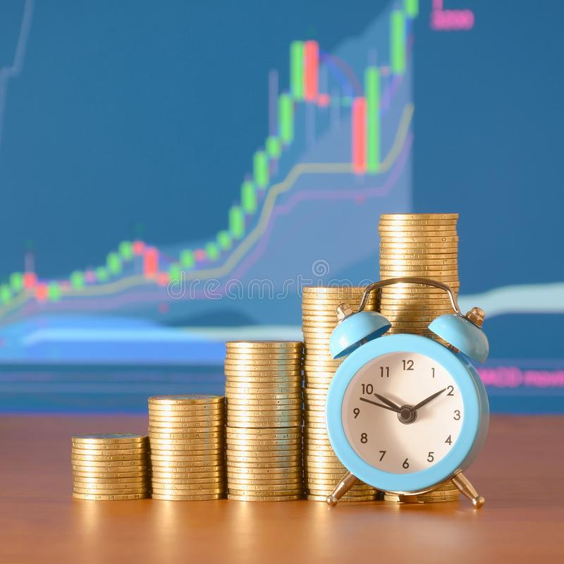 Time for savings money concept, banking and business idea. Alarm clock and Money coin stacks in grow graph. Finance sustainable development and economic growth stock photos