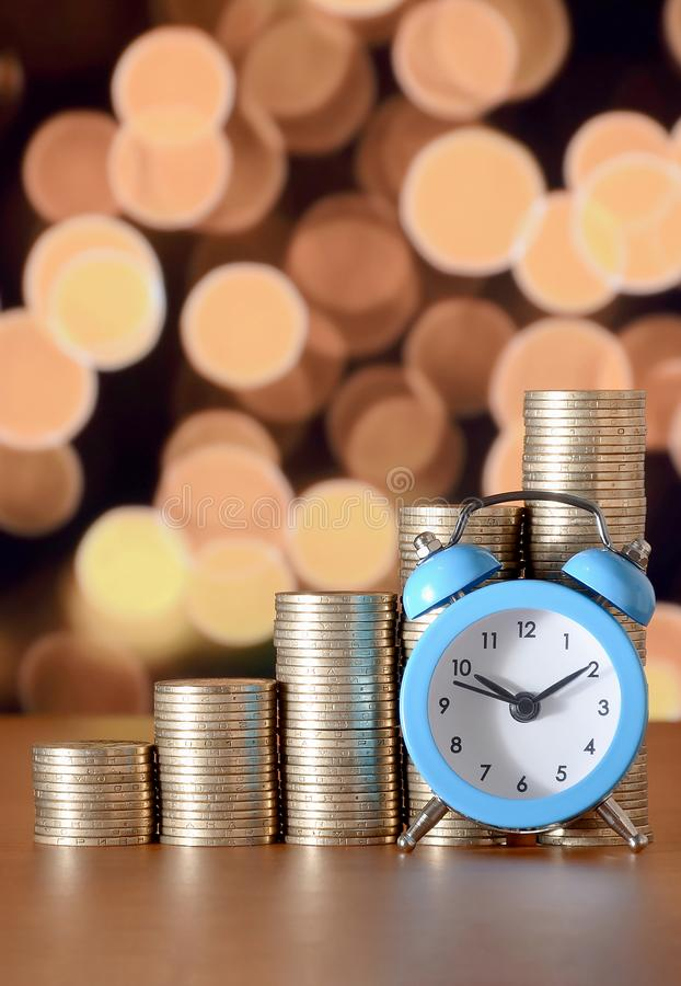 Time for savings money concept, banking and business idea. Alarm clock and Money coin stacks in grow graph. Finance sustainable development and economic growth royalty free stock photos