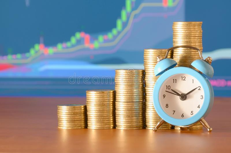 Time for savings money concept, banking and business idea. Alarm clock and Money coin stacks in grow graph. Finance sustainable development and economic growth stock image