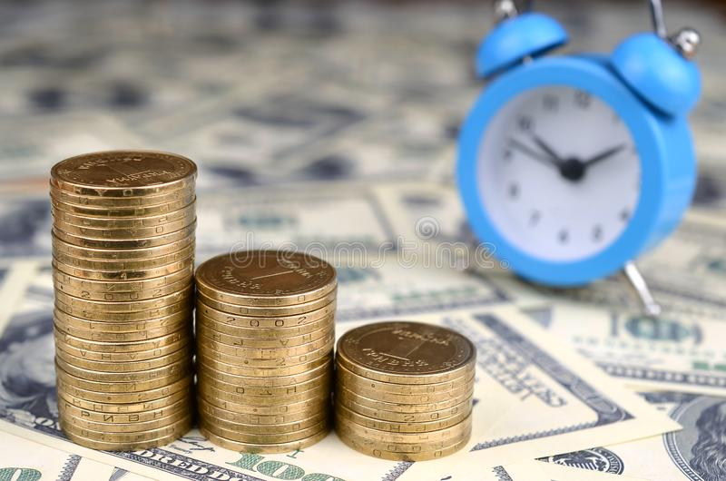 Time for savings money concept, banking and business idea. Alarm clock and Money coin stacks on many dollar bills. Finance sustainable development and economic stock image