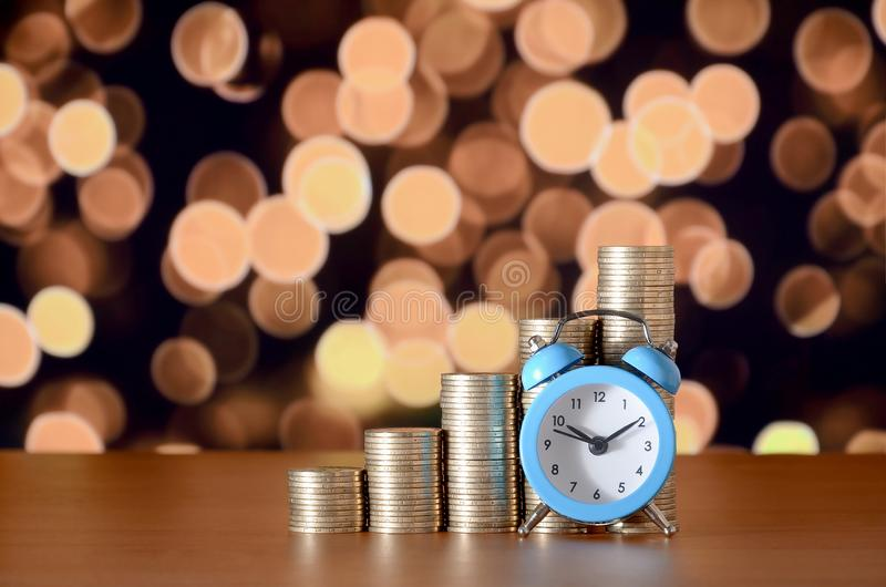 Time for savings money concept, banking and business idea. Alarm clock and Money coin stacks in grow graph. Finance sustainable development and economic growth stock photography