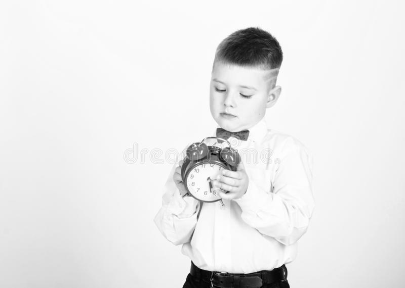 It is time. Schedule and timing. Morning routine. Schoolboy with alarm clock. Kid adorable boy white shirt red bow tie. Develop self discipline. Set up alarm royalty free stock images