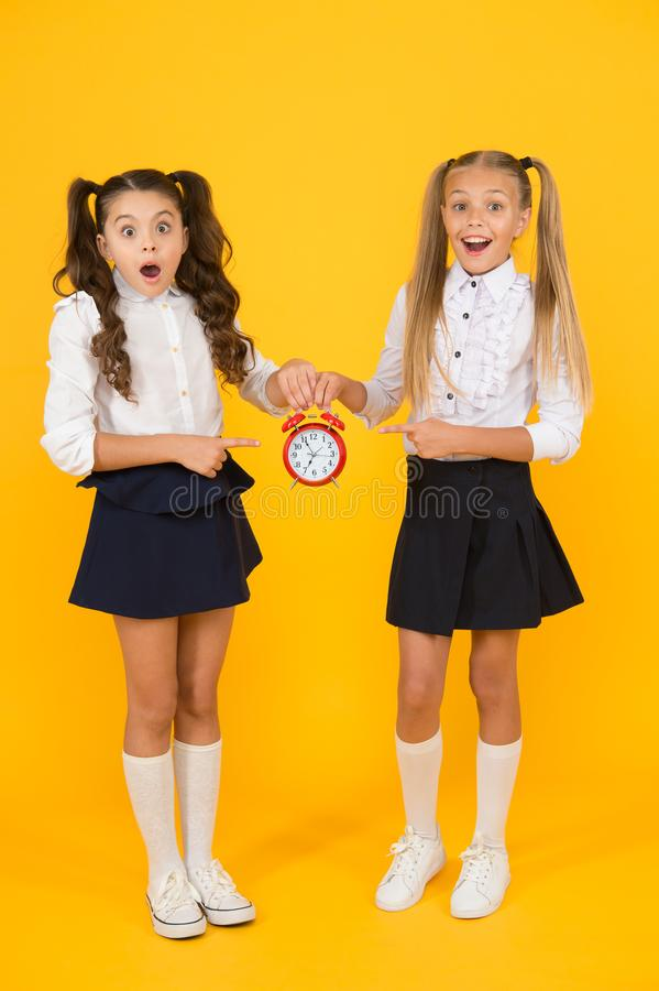 It is time. School schedule. Schoolgirls and alarm clock. Children school pupils. Knowledge day. School time. Surprised. Shocked kids hold alarm clock counting stock image