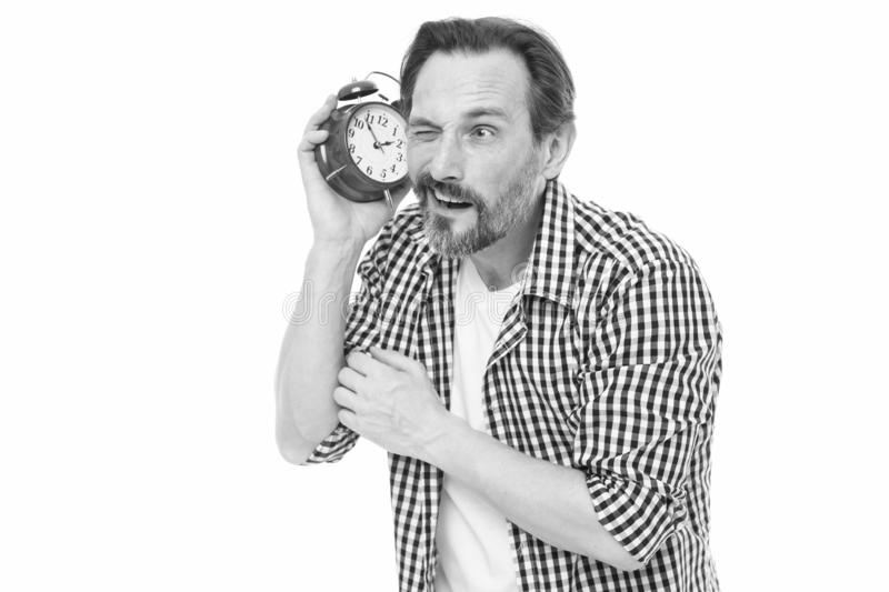 Time is short. Bearded man listening to clock ticking sound. Aged man holding alarm clock. Mature man with mechanical. Clock in hand. Senior timekeeper with stock images