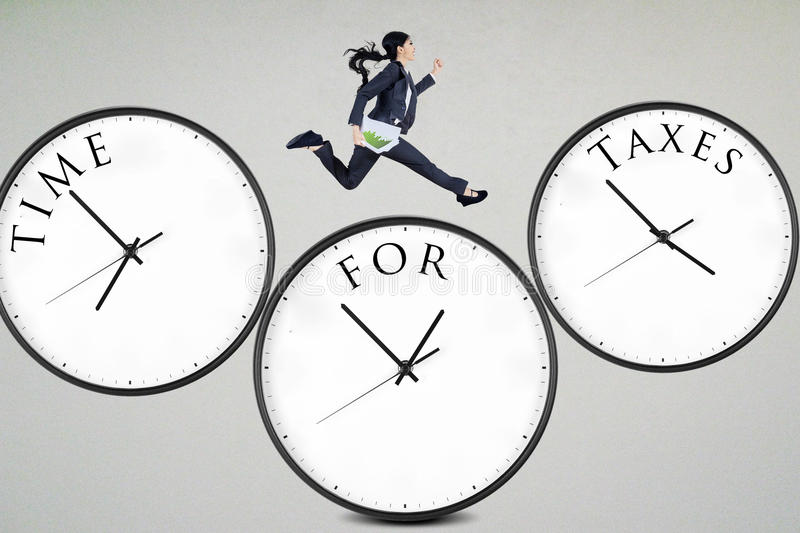 Time for taxes. Businesswoman running over the clocks with time for taxes stock photos