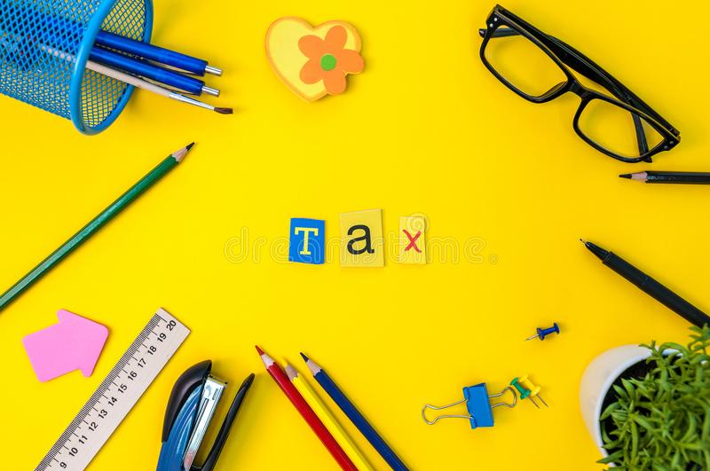 Time for Taxes. Money Financial Accounting. Taxation Concept with office suplies at yellow background royalty free stock photos