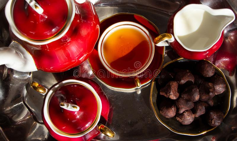 Time for a tea break. Cups of hot drink, candy and hearts stock photos
