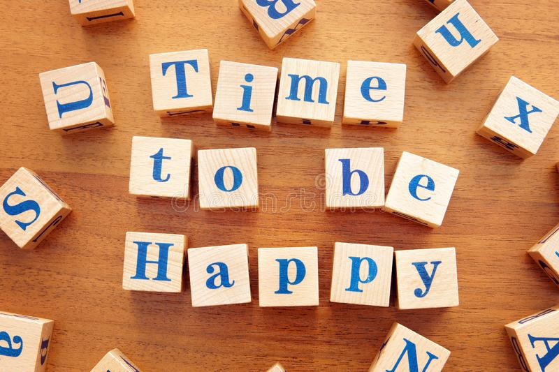 Time to be happy. Conceptual image with the text made from wooden cubes. On a desk royalty free stock photos