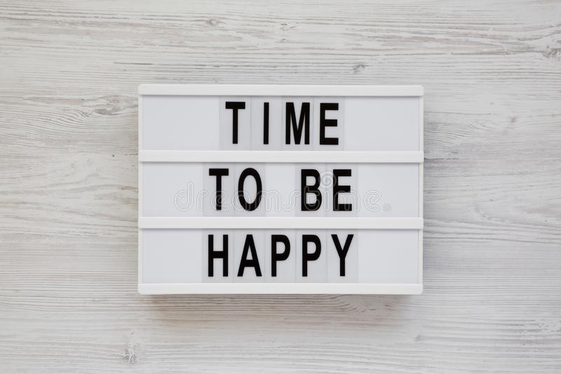 `Time to be happy` words on a modern board on a white wooden background, top view. Overhead, from above. Flat lay. Closeup royalty free stock photos