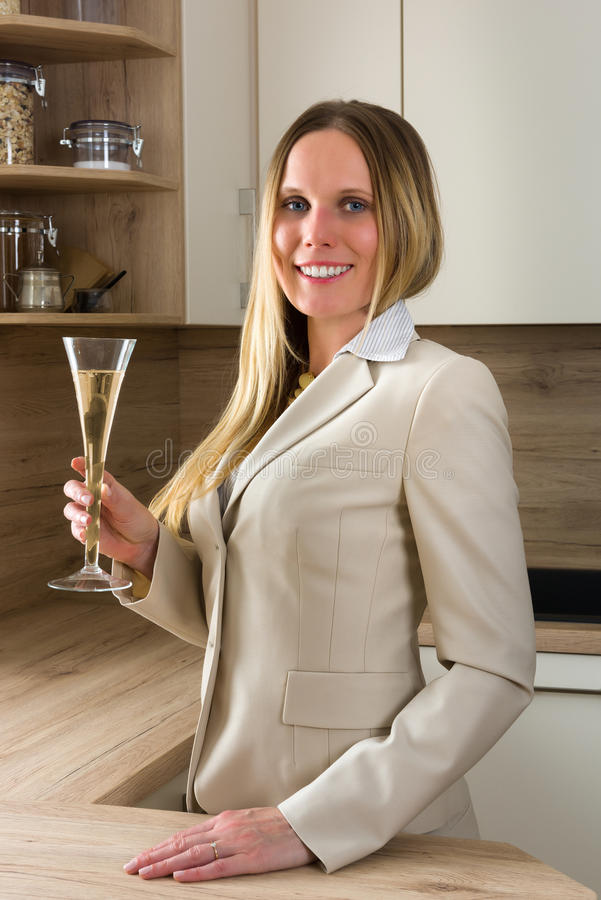 Time to celebrate: business woman with a glass of champagne. Relaxing in a modern kitchen stock photos