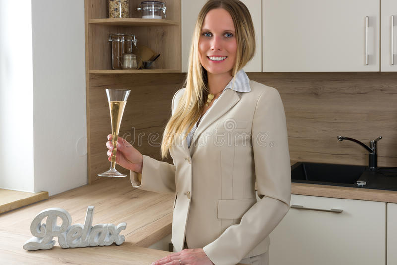 Time to celebrate: business woman with a glass of champagne. Relaxing in a modern kitchen stock images