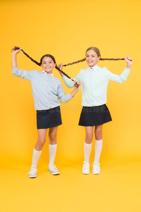 Time to chill. happy girls in school uniform. smart little girls on yellow background. kid fashion. Friendship and stock photography