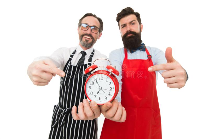 Time to cook. Men pointing at alarm clock. Man bearded hipster and mature chef apron white background. Cook dinner. We royalty free stock image