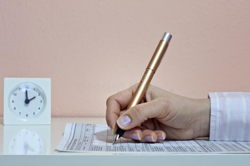 Time to fill out tax form. Women quickly completing tax form royalty free stock photography