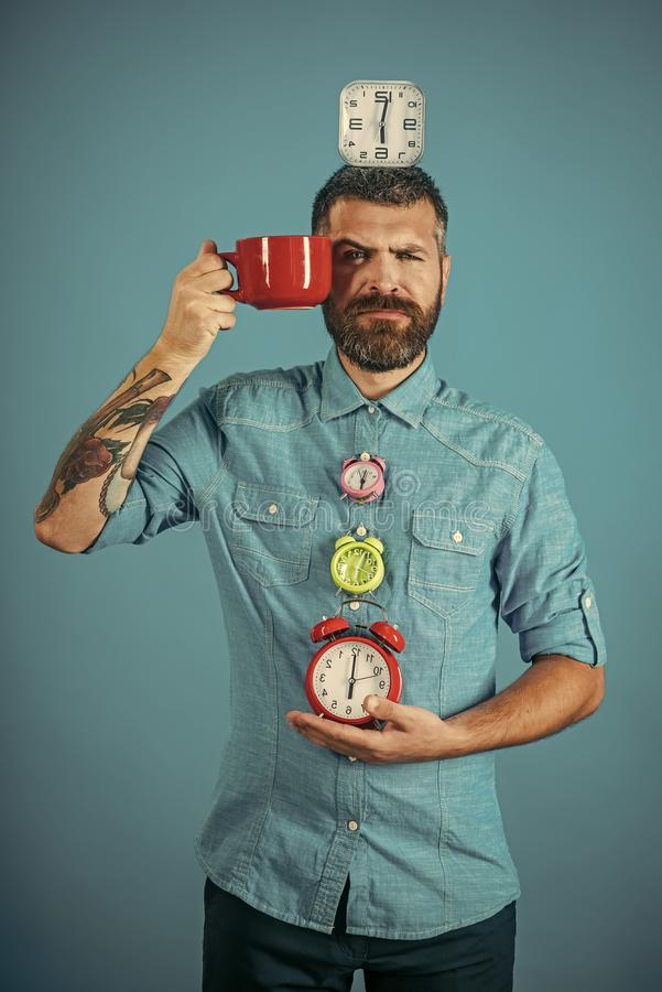 Time to get up. Man drink morning coffee or tea with alarm clock. Hipster with milk cup, time. guy with mulled wine, clock on blue background. Refreshment stock images
