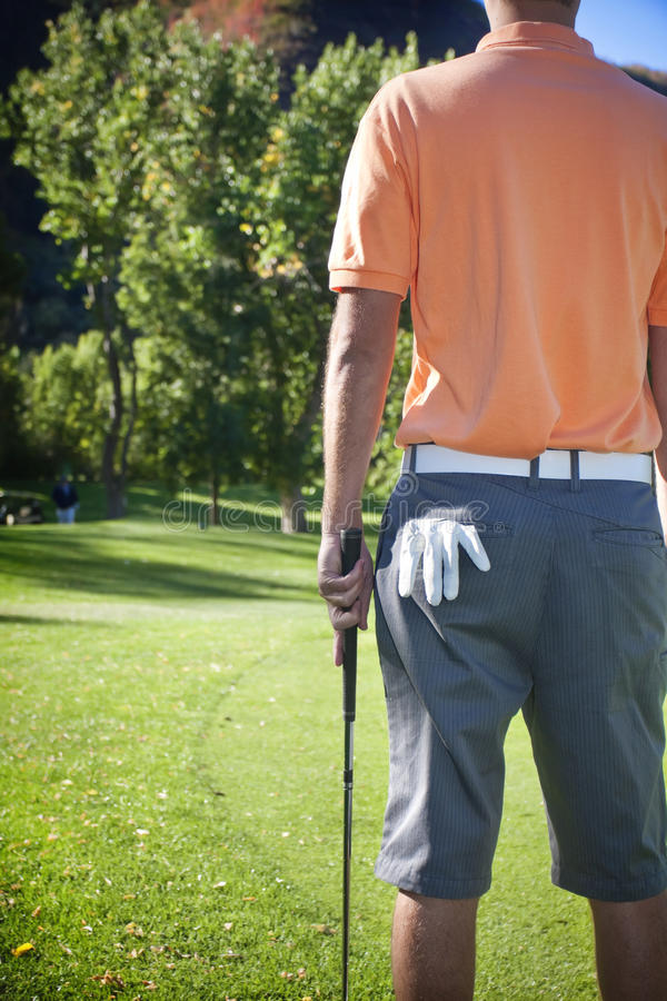 Time to go Golfing. A rear view photo of a golfer standing around the green of a golf course. Good generic photo of the golfing industry royalty free stock photography